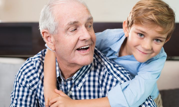Portrait of happy little Caucasian boy embracing his senior grandfather, looking at camera and smiling. Senior man looking at grandchild
