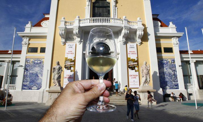 Um copo de vinho na mão com o pavilhão como pano de fundo.
